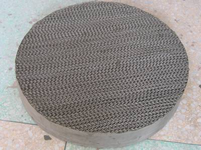 There is a piece of metal wire gauze structured packing set on the ground.